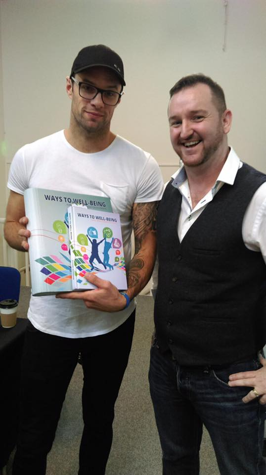Bressie and Feidhlim with our Ways to Well-being programme book.